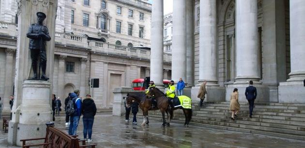 Police horses draw an audience outside The Royal Exchange in the rain.