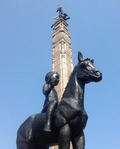"""Almaty Monument fronted by a toddler astride a foal. """"NP Horse, No Kazakhstan"""